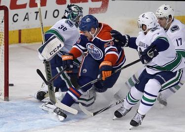 The Edmonton Oilers' Matt Hendricks (23) is stopped by the Vancouver Canucks' goalie Ryan Miller (30), Yannick Weber (6) and Radim Vrbata (17) during third period NHL action at Rexall Place, in Edmonton Alta., on Wednesday Nov. 19, 2014. The Canucks won 5-4. David Bloom/Edmonton Sun/QMI Agency