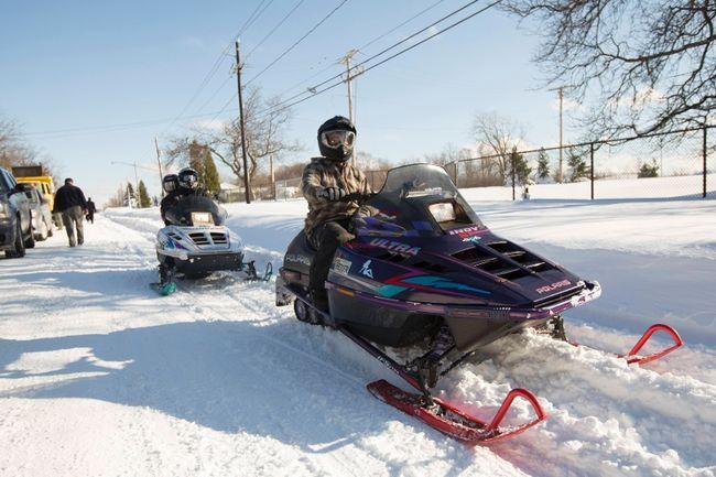 People ride snowmobiles through the streets in Buffalo, New York, November 21, 2014. (REUTERS/Lindsay DeDario)