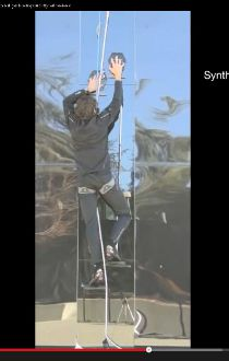Man climbing up wall in gecko gloves