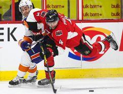 Ottawa Senators' Chris Phillips battles with New York Islanders' Frans Nielsen during NHL hockey action at the Canadian Tire Centre in Ottawa Thursday, December 4, 2014. Errol McGihon/Ottawa Sun/QMI Agency