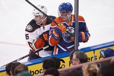 Edmonton forward David Perron (57) is checked by Anaheim defenceman Ben Lovejoy (6) during the third period of a NHL hockey game between the Edmonton Oilers and Anaheim Ducks at Rexall Place in Edmonton, Alta., on Friday, Dec. 12, 2014. The Ducks won 4-2. Ian Kucerak/Edmonton Sun/ QMI Agency