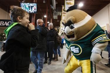 Brothers Matthew Getzinger, 7, gives his hat to Eskimos mascot Punter during the Edmonton Eskimos Locker Room Sale at Commonwealth Stadium in Edmonton, Alta., on Saturday, Dec. 13, 2014. Ian Kucerak/Edmonton Sun/ QMI Agency