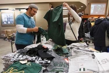 Lukas and Skylin Herba check out clothing during the Edmonton Eskimos Locker Room Sale at Commonwealth Stadium in Edmonton, Alta., on Saturday, Dec. 13, 2014. Ian Kucerak/Edmonton Sun/ QMI Agency