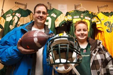 Scott and Ryan Kilborn, 12, show off some of their Eskimos equipment finds during the Edmonton Eskimos Locker Room Sale at Commonwealth Stadium in Edmonton, Alta., on Saturday, Dec. 13, 2014. Ian Kucerak/Edmonton Sun/ QMI Agency