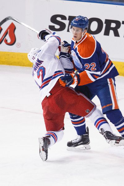 Edmonton defenceman Keith Aulie (22) takes down New York forward Lee Stempniak (12) during the second period of a NHL hockey game between the Edmonton Oilers and New York Rangers at Rexall Place in Edmonton, Alta., on Sunday, Dec. 14, 2014. Ian Kucerak/Edmonton Sun/ QMI Agency