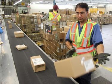 Canada Post worker Manjeet Bedi unloads incoming mail at the main post office in Winnipeg, Man. Monday December 15, 2014. Brian Donogh/Winnipeg Sun/QMI Agency