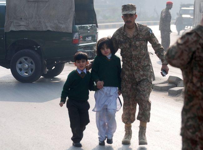 A soldier escorts schoolchildren from the Army Public School that is under attack by Taliban gunmen in Peshawar, December 16, 2014. (REUTERS/Khuram Parvez)