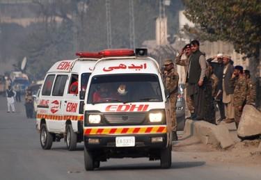 Ambulances drive away from a military run school that is under attack by Taliban gunmen in Peshawar, December 16, 2014. (REUTERS/Khuram Parvez)