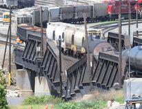 Workers drain the tanks of a train as it teeters with six cars on Bonnybrook Bridge in Calgary, Alta., on June 27, 2013. The bridge sank as the train was crossing on it. (Stuart Dryden/QMI Agency)
