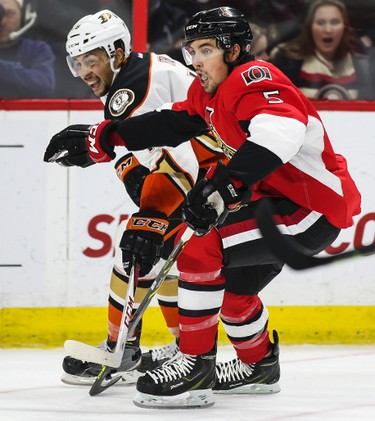 Ottawa Senators' Cody Ceci battles with Anaheim Ducks' Emerson Etem during NHL hockey action at the Canadian Tire Centre in Ottawa, Ontario on Friday December 19, 2014. Errol McGihon/Ottawa Sun/QMI Agency