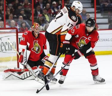 Ottawa Senators' Erik Karlsson battles for a loose puck with Anaheim Ducks' Ryan Kesler in front of Sens netminder Craig Anderson during NHL hockey action at the Canadian Tire Centre in Ottawa, Ontario on Friday December 19, 2014. Errol McGihon/Ottawa Sun/QMI Agency