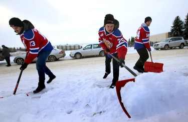 Team members Brandon Baddock (13), Lane Baouer (25) and Aaron Irving shovels some sidewalks in the Allendale area. Edmonton Oil Kings help launch 2015 Snow Angels program in Edmonton, Alta., on Wednesday Jan.7, 2015.  Perry Mah/Edmonton Sun/QMI Agency