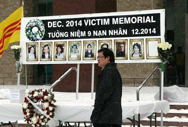 A man walks past a display at a vigil for the mass murder victims at City Hall in Edmonton, Alta., on Saturday Jan.10 2015. Perry Mah/Edmonton Sun/QMI Agency