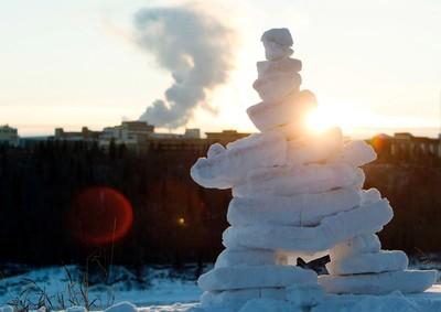 The Sun sets behind an inukshuk made out of snow, in Constable Ezio Faraone Park, in Edmonton Alta., on Sunday Jan. 4, 2015. David Bloom/Edmonton Sun/QMI Agency