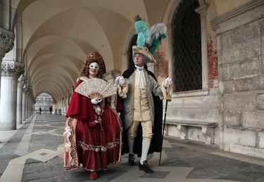 Masked revellers walk near Saint Mark's Square during the Venetian Carnival in Venice January 31, 2015. REUTERS/Stefano Rellandini