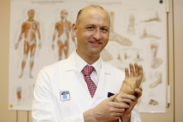 Austrian surgeon Oskar Aszmann, head of plastic surgery at the Medical University of Vienna, shows a bionic hand on Feb. 24, 2015 in Vienna. (AFP PHOTO/DIETER NAGL)