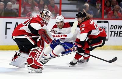 Ottawa Senators goaltender Andrew Hammond stops a shot by Montreal Canadiens Max Pacioretty as Sens Erik Karlsson defends during NHL hockey action at the Canadian Tire Centre on Wednesday February 18, 2015. Errol McGihon/Ottawa Sun/QMI Agency