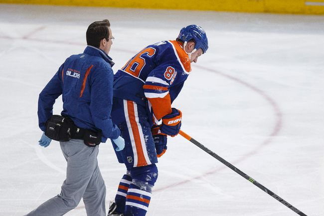 Edmonton defenceman Nikita Nikitin (86) skates off the ice with a team medical staffer trailing after a hit in a game against Buffalo0 in January. (Ian Kucerak, Edmonton Sun)