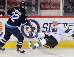 Winnipeg Jets right winger Chris Thorburn (l) dumps San Jose Sharks defenceman Justin Braun during NHL hockey in Winnipeg, Man. Tuesday, March 17, 2015. Brian Donogh/Winnipeg Sun/QMI Agency