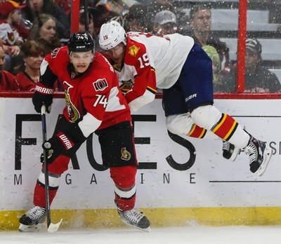 Ottawa Senators Mark Borowiecki checks Florida Panthers Scottie Upshall into the end boards during NHL hockey action at the Canadian Tire Centre in Ottawa, Ontario on March 29, 2015. Errol McGihon/Ottawa Sun/QMI Agency