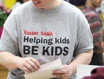 Jennifer MacDonald speaks with volunteers manning phones during Easter Seals telethon on March 29, 2015.