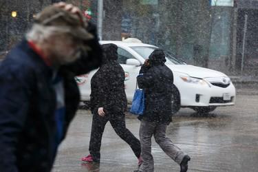 Edmontonians walk in the driving wind and snow across Jasper Avenue in downtown Edmonton, Alta., on Wednesday, April 1, 2015. Ian Kucerak/Edmonton Sun/ QMI Agency