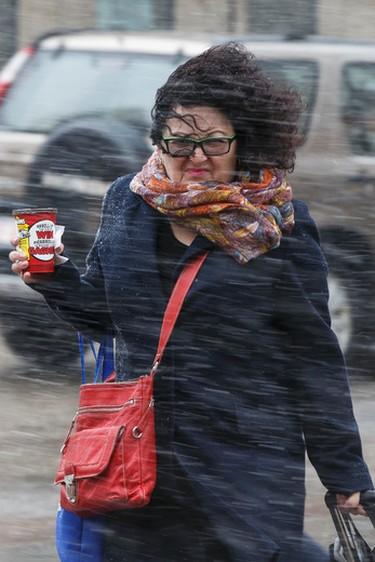 A woman crosses the street in the driving wind and snow along Jasper Avenue in downtown Edmonton, Alta., on Wednesday, April 1, 2015. Ian Kucerak/Edmonton Sun/ QMI Agency