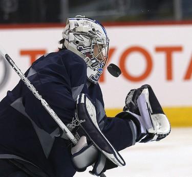 Winnipeg Jets goalie Connor Hellebuyck blocks a shot during a light skate in Winnipeg, Man. Tuesday April 21, 2015. Brian Donogh/Winnipeg Sun/Postmedia Network
