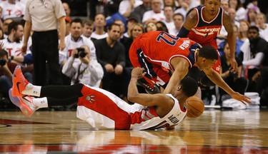 Toronto Raptors' DeMar DeRozan (10) and Washington Wizards' Otto Porter Jr. (22) crash to the court on April 21. (Jack Boland/Toronto Sun/Postmedia Network)