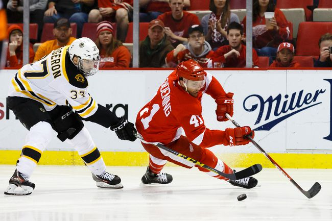 Boston Bruins centre Patrice Bergeron (left) trips Detroit Red Wings forward Luke Glendening (41) during NHL play at Joe Louis Arena. (Rick Osentoski/USA TODAY Sports)