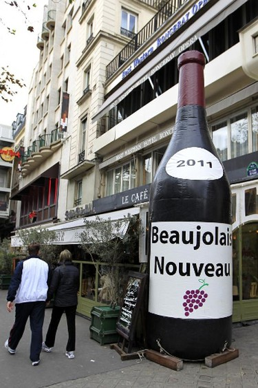 People walk past a giant inflatable bottle of the 2011 Beaujolais Nouveau wine in Paris November 18, 2011. REUTERS/Charles Platiau