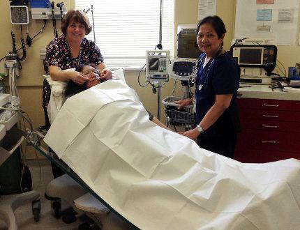 Nurses Bonnie Byrne (left) and Carmelita Escasa treat housekeeper Bella Beardy, posing as a patient, in the emergency room at Bearskin Lake First Nation nursing station.