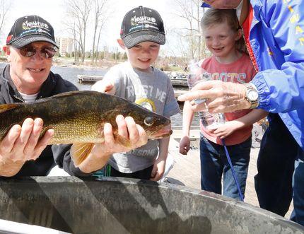 Jason Miller/The Intelligencer Gerry Jowett show his grandchildren, Allie and Ryan his catch of the day Saturday during the Trenton Kiwanis walleye World Fishing Derby.