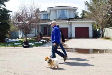 Pedestrians walk past the west Edmonton home where Omar Khadr will be staying with his lawyer Dennis Edney, in Edmonton, Alta. on Thursday May 7, 2015. David Bloom/Edmonton Sun/Postmedia Network