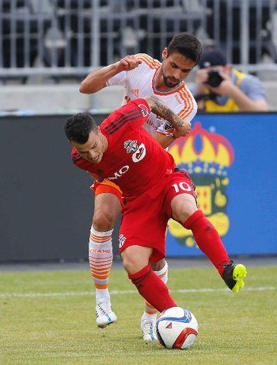 Sebastian Giovinco battles a Houston player  as Toronto FC host Houston Dynamo at the refurbished BMO Field  during MLS action in Toronto, Ont. on Sunday May 10, 2015. Michael Peake/Toronto Sun