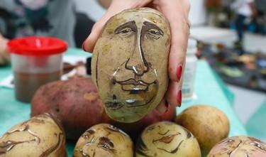 Russian cartoon artist Daria Chebunina shows a potato displaying the image of Russia's President Vladimir Putin during a food fair in Krasnoyarsk, September 20, 2014. REUTERS/Ilya Naymushin