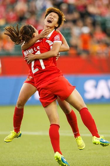 China's Wang Lisi (21) celebrates her goal with Lou Jiahui (16) against the Netherlands during a FIFA Women's World Cup 2015 match at Commonwealth Stadium in Edmonton, Alta., on Thursday June 11, 2015. Ian Kucerak/Edmonton Sun/Postmedia Network