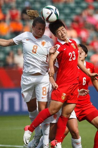 Netherlands' Sherida Spitse (8) and China's Ren Guixin (23) jump for a flying ball during a FIFA Women's World Cup 2015 match at Commonwealth Stadium in Edmonton, Alta., on Thursday June 11, 2015. Ian Kucerak/Edmonton Sun/Postmedia Network