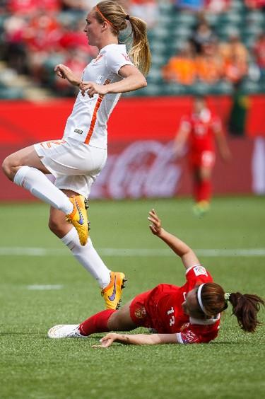 Netherlands' Desiree van Lunteren (2) trips on China's Tang Jiali (13) during a FIFA Women's World Cup 2015 match at Commonwealth Stadium in Edmonton, Alta., on Thursday June 11, 2015. Ian Kucerak/Edmonton Sun/Postmedia Network