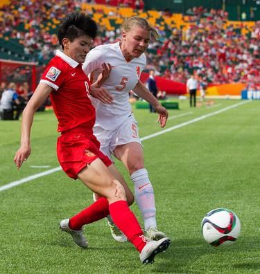 Team China's Wang Shanshan (9) battles the Netherlands' Petra Hogewoning (5) during FIFA Women's World Cup Canada 2015 action at Commonwealth Stadium, in Edmonton Alta. on Thursday June 11, 2015. David Bloom/Edmonton Sun/Postmedia Network
