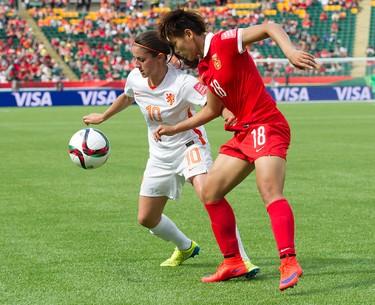 Team China's Han Peng (18) battles the Netherlands' Dani�lle van de Donk (10) during FIFA Women's World Cup Canada 2015 action at Commonwealth Stadium, in Edmonton Alta. on Thursday June 11, 2015. China won 1-0. David Bloom/Edmonton Sun/Postmedia Network