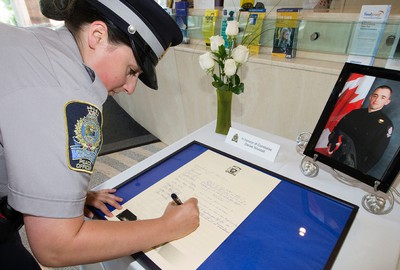 Peace Officer Eden McCartney signs a book of condolence for Cst. Daniel Woodall at City Hall, in Edmonton Alta. on Wednesday June 10, 2015. David Bloom/Edmonton Sun/Postmedia Network