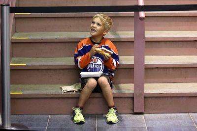 6 year old David Morland enjoys a hotdog at the Edmonton Oiler Draft Party at Rexall Place in Edmonton, Alberta Friday, June 26, 2015.Perry Mah/Edmonton Sun/Postmedia Network