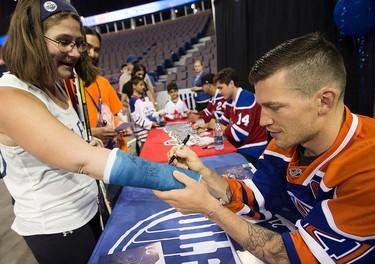 Edmonton Oilers' Andrew Ference signs Ashley Black's cast during the Edmonton Oilers Locker Room Sale at Rexall Place, in Edmonton Alta. on Saturday June 27, 2015. David Bloom/Edmonton Sun/Postmedia Network
