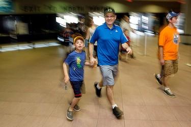 Manuel Mendes and his grandson Mateo Pereira, 8, rush into the Edmonton Oilers Locker Room Sale at Rexall Place, in Edmonton Alta. on Saturday June 27, 2015. David Bloom/Edmonton Sun/Postmedia Network