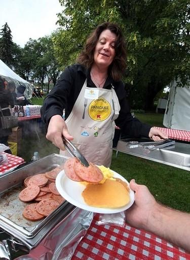 Lori Sigurdson,Minister of Innovation and Advance Education serves some turkey sausage during the 2015 Premier Pancake Breakfast at the Alberta Legislature grounds in Edmonton, Alta., on Thursday July 16, 2015. Perry Mah/Edmonton Sun/Postmedia