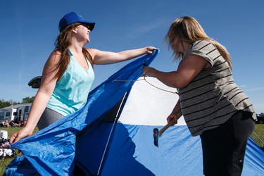 Cat Sorensen (left), and Alex Ford, both from Calgary, setup their tent during Big Valley Jamboree 2015 in Camrose, Alta. on Thursday July 30, 2015. Ian Kucerak/Edmonton Sun/Postmedia Network