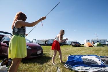 Sisters Kristy (left) and Frankie Dziuba set up their tent during Big Valley Jamboree 2015 in Camrose, Alta. on Thursday July 30, 2015. Ian Kucerak/Edmonton Sun/Postmedia Network