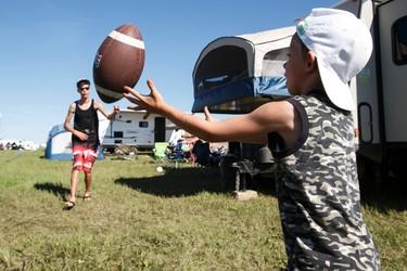 Edmontonians Brock Delorme, 17, (left) and Ryan Blake, 6, play football at their family campsite during Big Valley Jamboree 2015 in Camrose, Alta. on Thursday July 30, 2015. Ian Kucerak/Edmonton Sun/Postmedia Network