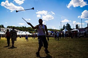 Kain Luciow spins devil sticks during the Edmonton Folk Music Festival at Gallagher Park in Edmonton, Alta. on Saturday, Aug. 8, 2015. Codie McLachlan/Edmonton Sun/Postmedia Network
